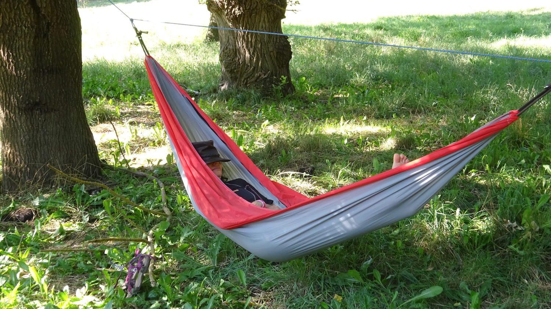 Hamac planté entre deux arbres, herbe fraîche et personne dormant avec un chapeau