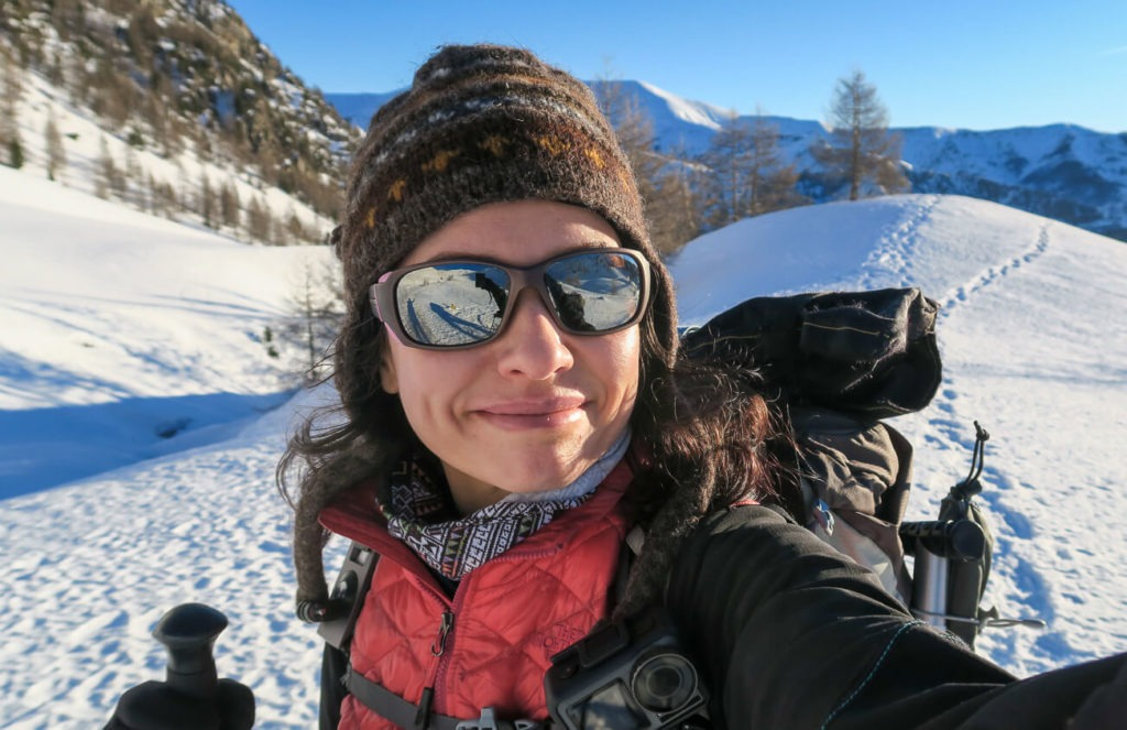 Aude avec lunettes de soleil et bonnet sur fond de montagnes enneigées