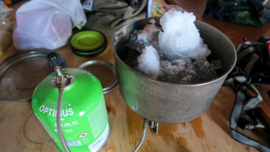 Réchaud à gaz et casseroler remplie de neige à faire fondre