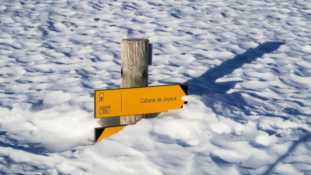 Panneau de signalisation sous la neige indiquant la cabane de Joyeux