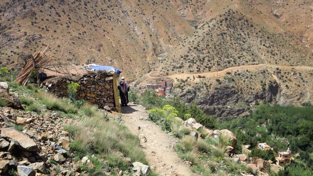Homme en djellaba sur un chemin montagneux dans la vallée de l'Ourika au Maroc, avec village berbère en fond