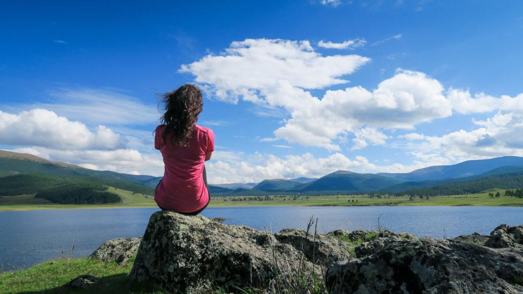 Femme assise de dos devant un lac en Mongolie