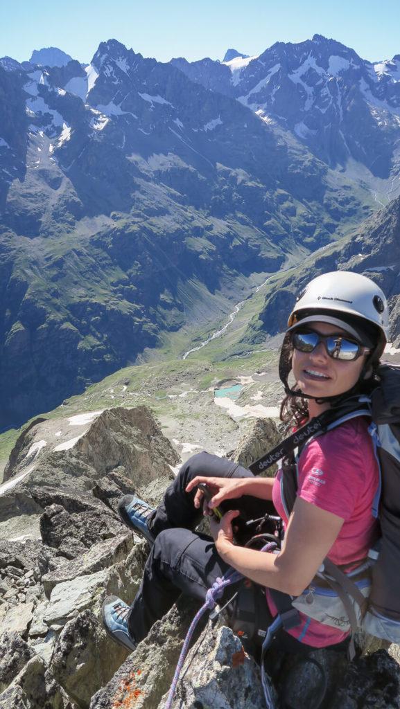 Femme avec casque en tenue d'alpinisme au sommet du Bec de Canard, vallée de la Lavey