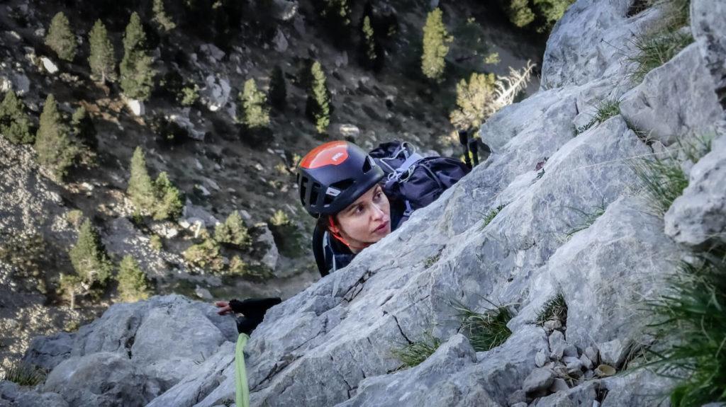 Femme avec casque d'escalade sous une pente de rocher