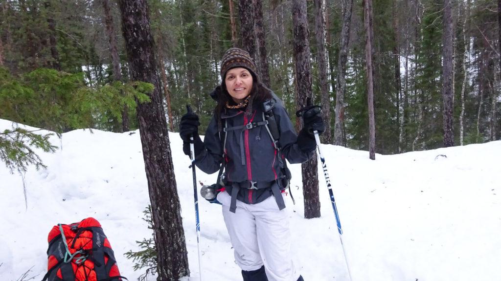 Portrait de femme dans la forêt avec bâtons de randonnée et sac à dos