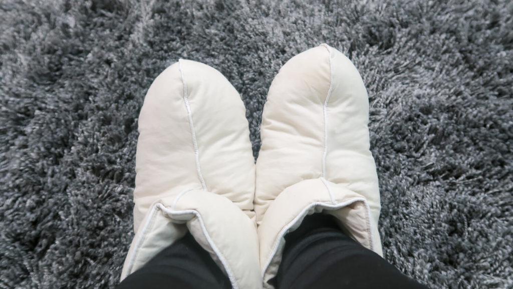chaussons-en-duvet-sur-tapis-moelleux-gris