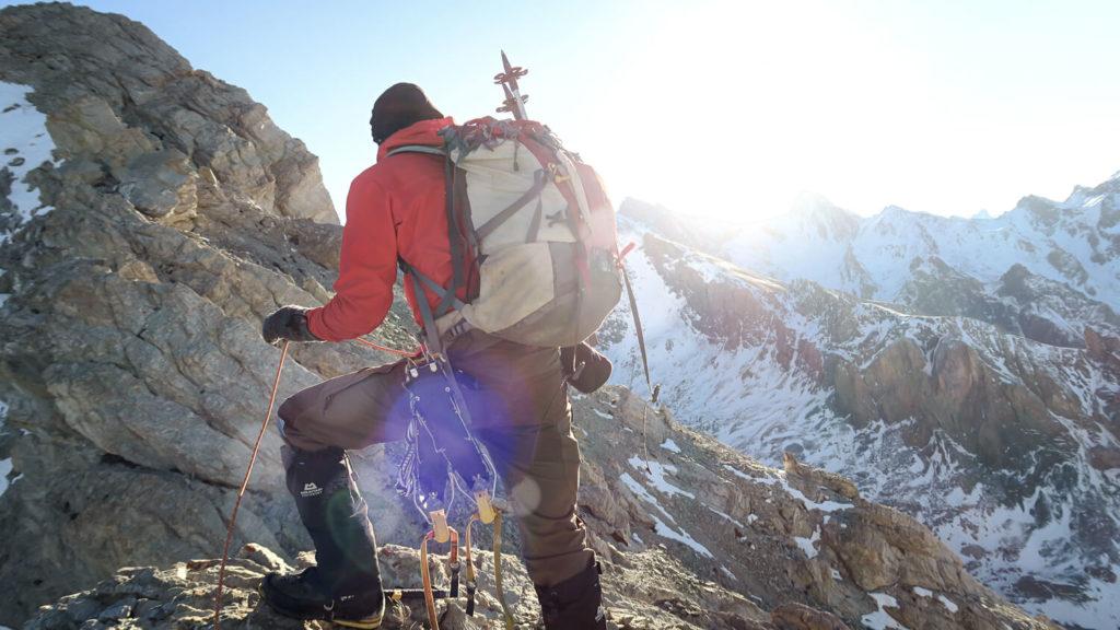 Homme de dos avec sac et matériel d'alpinisme, en montagne
