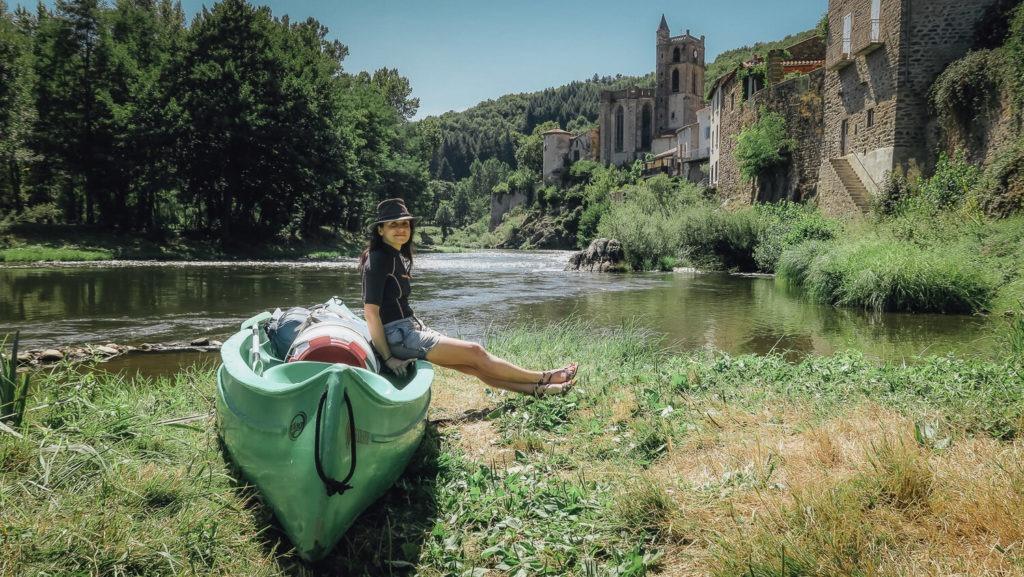 Je suis assise avec mon chapeau sur le canoë devant le village de Lavoûte-Chilhac lors d'une randonnée en canoë sur l'Allier