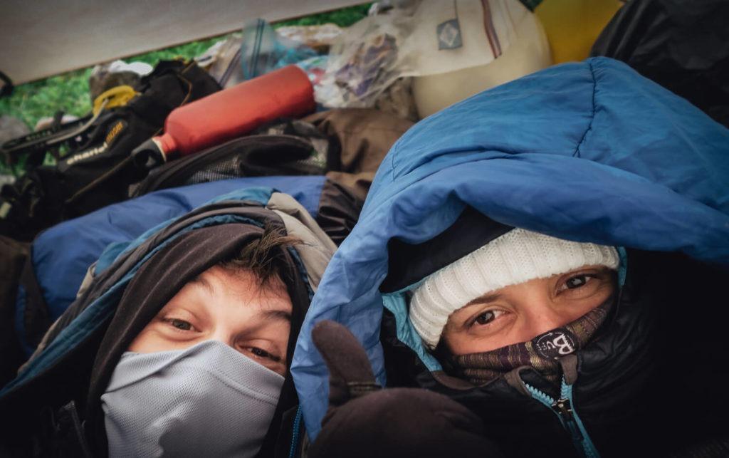 Deux personnes dans leurs duvets sous la tente, en montagne, le cache-col remonté sur le nez