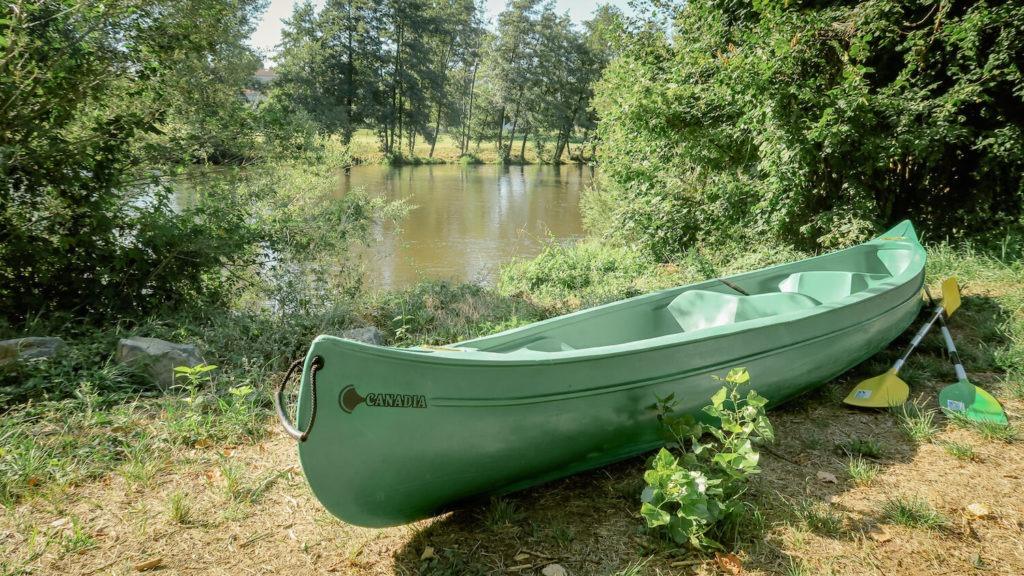 canoë vert posé sur l'herbe la rive de l'Allier avec pagaies