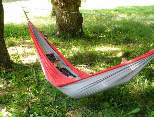 Je fais la sieste avec un chapeau sur le nez, dans un hamac tendu entre deux gros arbre sur un pré d'herbe verte