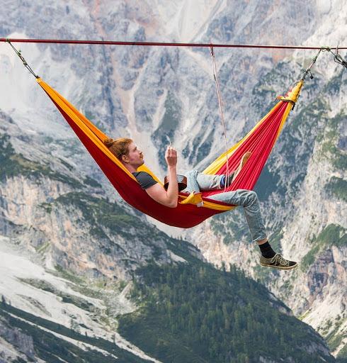 Homme installé dans un hamac suspendu au-dessus du vide, dans les montagnes