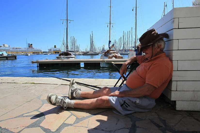 Un homme fait la sieste assis sur la jetée d'un port