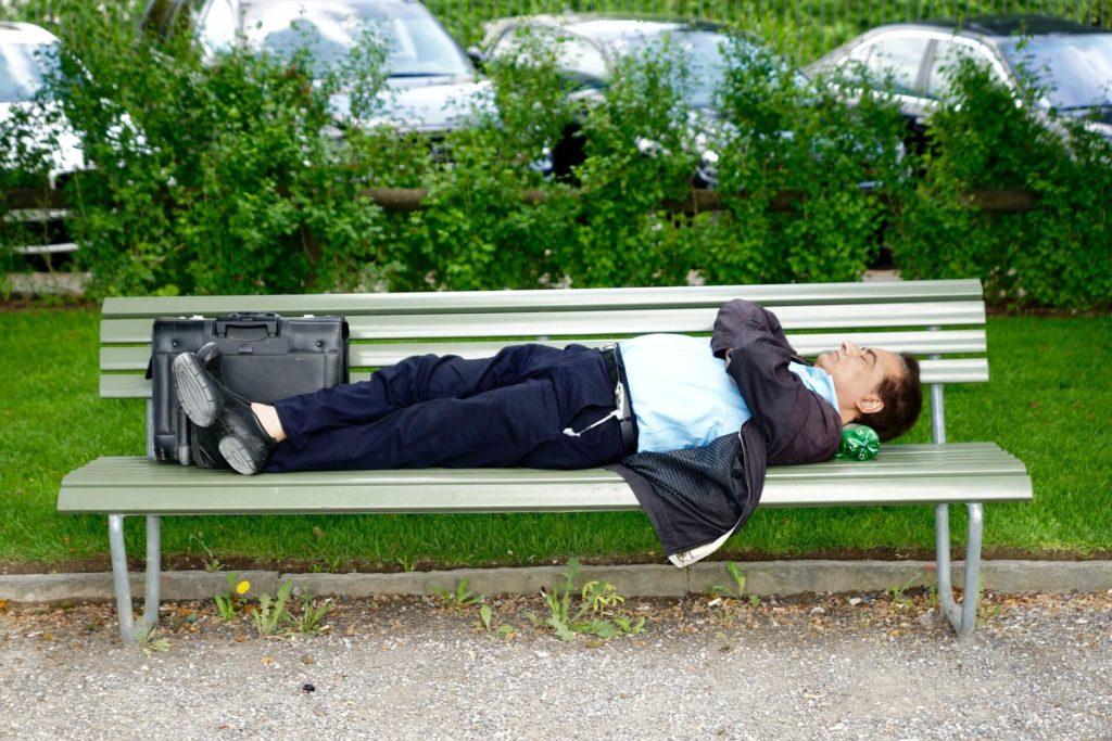 Un homme fait une sieste dans un parc, allongé sur un banc