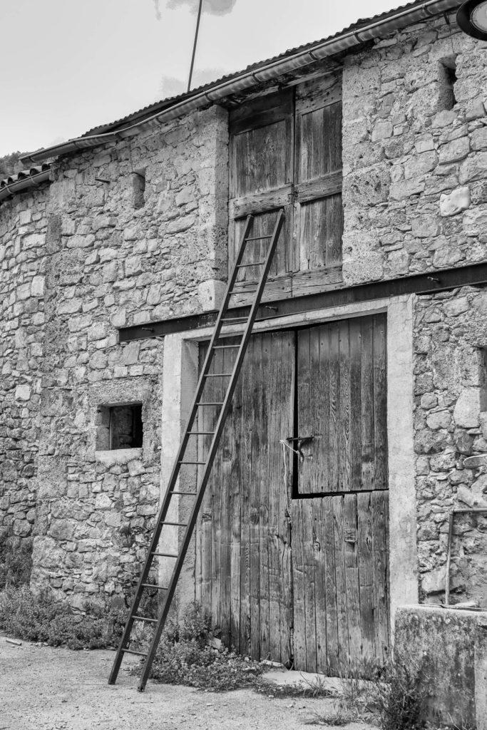 Cliché noir et blanc d'une grange traditionnelle avec échelle dans le village des Cuns en Aveyron