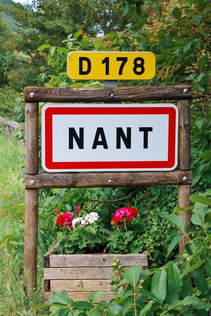 Panneau de signalisation du village de Nant avec géraniums où il est bon de faire un stop lors d'un weekend en Aveyron