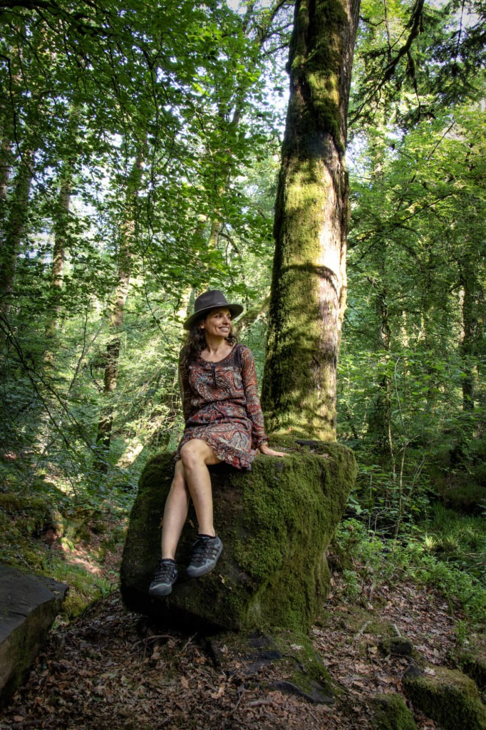 Femme assise sur un rocher au pied d'un arbre