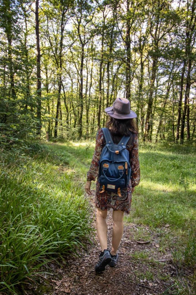 Femme avec chapeau marchant dans la forêt d'Huelgoat