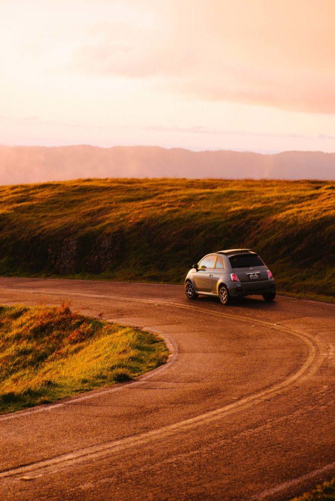 Fiat 500 roulant sur une route au coucher du soleil