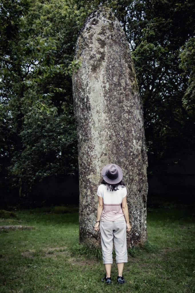 Femme avec chapeau devant de menhir de Kérampeulven