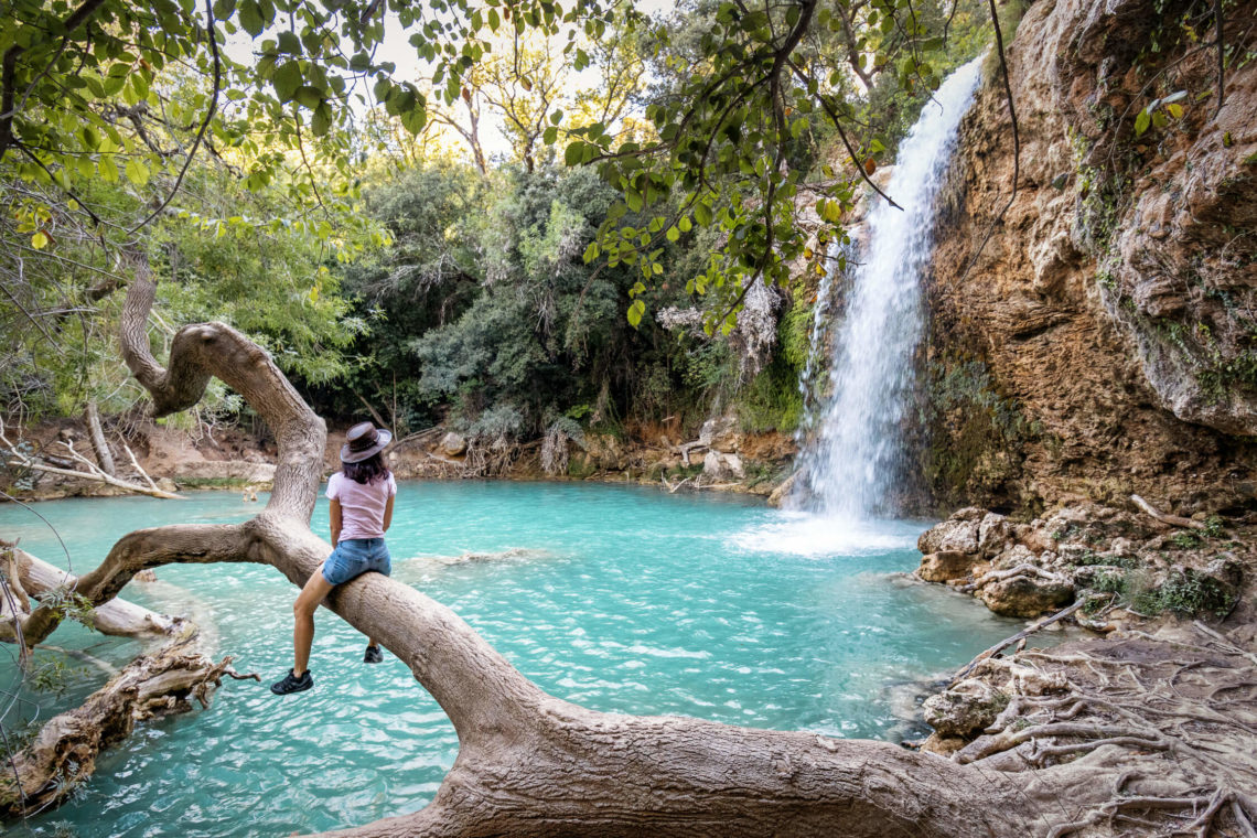 Femme avec chapeau assise sur un tronc d'arbre près de la petite cascade de Sillans
