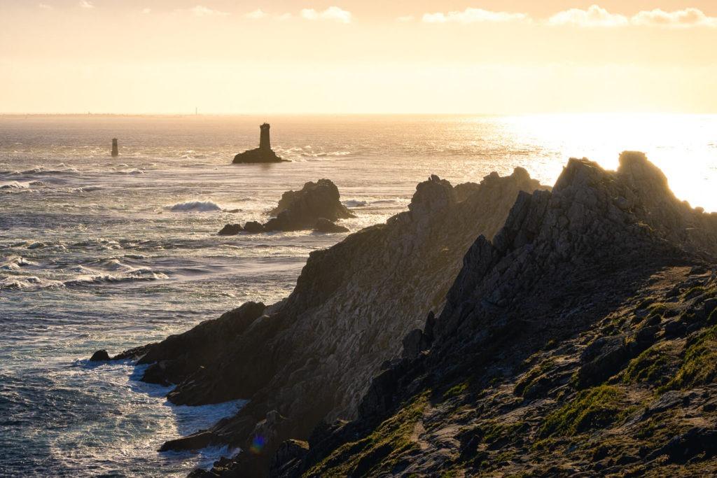 Le phare de La Vieille à la Pointe du Raz, au coucher du soleil devant les rochers de la côte