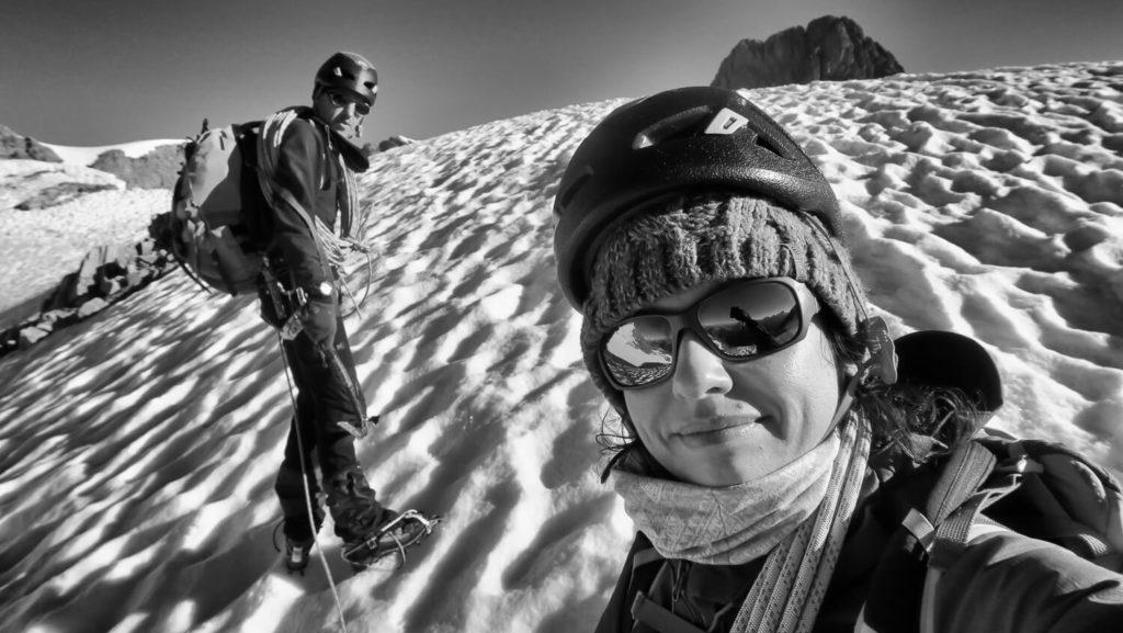 Duo homme et femme en alpinisme, sur une pente de neige avec casques et cordes