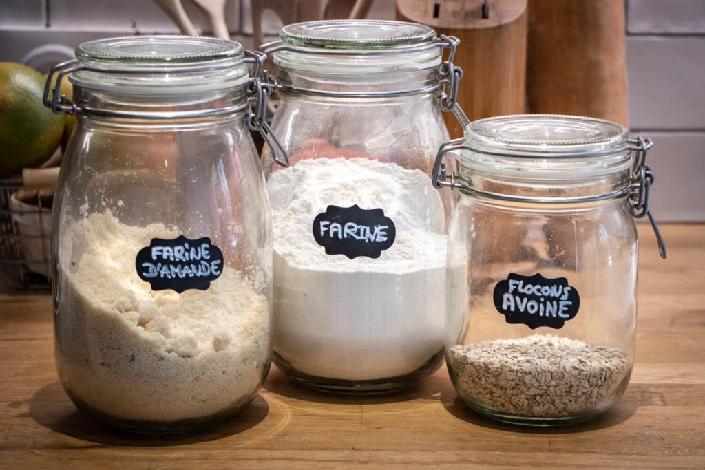 Bocaux de cuisine contenant de la farine, de la poudre d'amande et des flocons d'avoine pour préparation de pancakes vegan