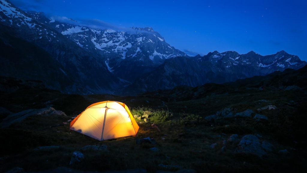 Tente éclairée de l'intérieur sur emplacement de bivouac à la tombée de la nuit, en montagne