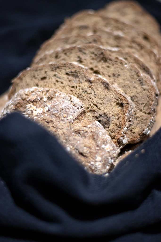 """Pain spécial sans gluten découpé en tranches, déposé sur un torchon noir, issu de la boulangerie bio """"Au Rythme du Pain"""" à Montpellier"""